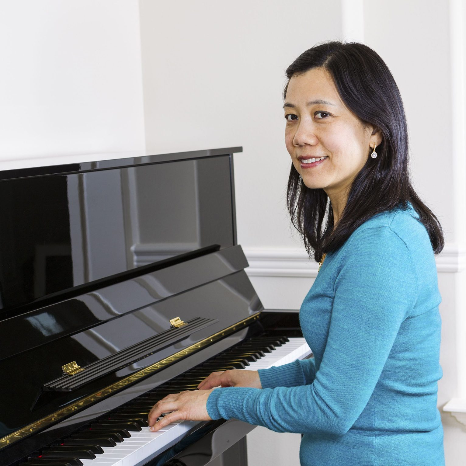 18286242 - vertical photo of mature woman playing piano with white walls in background