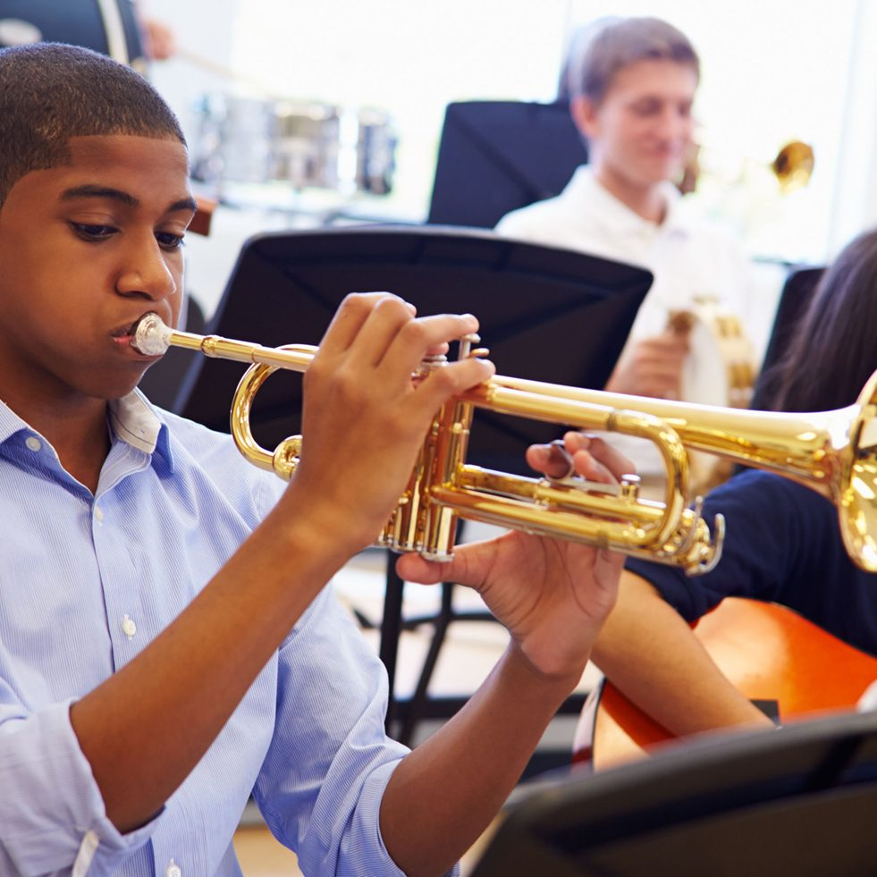 33479582 - male pupil playing trumpet in high school orchestra